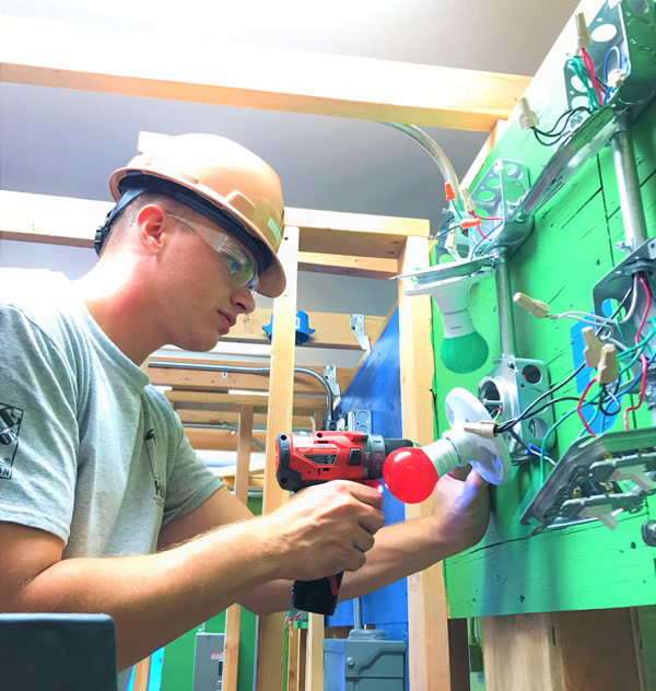 Electrician working on electrical wiring devices with protective glasses and helmet on