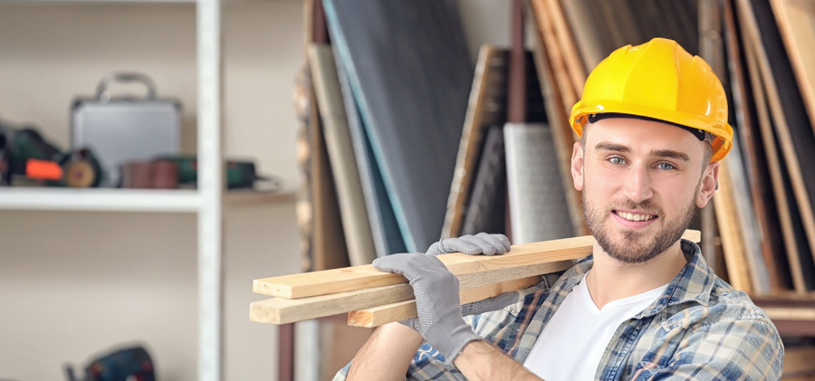 Construction worker lifting pieces of wood