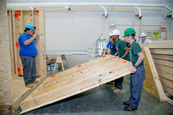 Several construction workers lifting a large wooden object