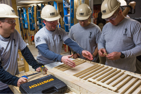 Craftsmen talking about the work on different pieces of wood